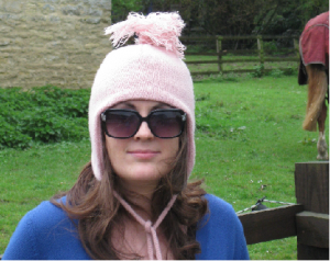 Woman posing in ski hat and sunglasses in front of a horse