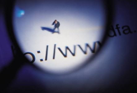 Magnifying glass held over a website address and a figurine of man