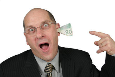 Bald man in a suit shouting with a 20 note in his ear