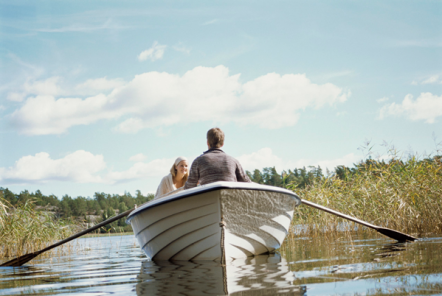 A man and a woman in a white row boat on a river on a sunny day
