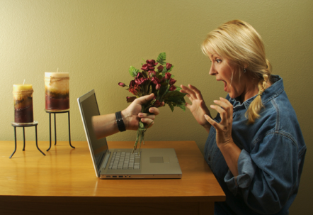 Man's hand appearing from a laptop with flowers in it. Woman looking shocked at the computer.