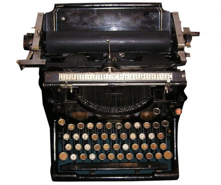 Black old-fashioned type writer with round metal keys