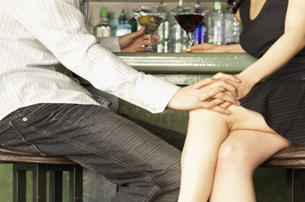 Man and a woman sitting holding hands at a bar with glasses of wine