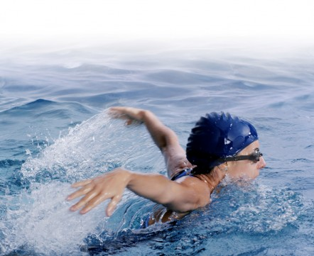 Woman swimming butterfly in a swim cap