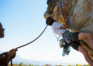 A man climbing up a rock with a woman supporting him