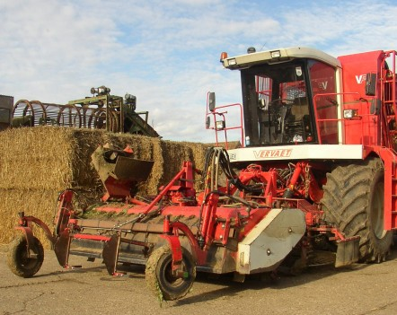 A red combine harvester next to bails of hay