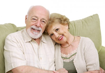 Picture of a couple in their 70s looking happy and sitting on a green sofa together