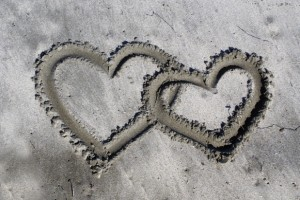 Black and white image of two interlinking hearts in the sand