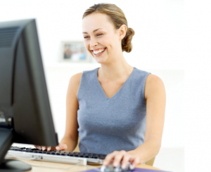 Woman in a blue vest laughing at a computer.