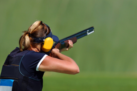 blonde woman in navy blue vest with yellow ear defenders and a gun