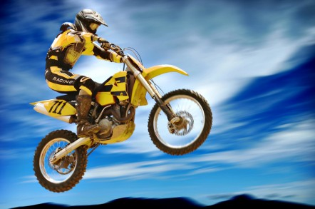A person in yellow leathers riding a yellow dirt bike