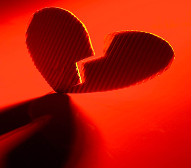 A red cardboard heart cut in half on a red background