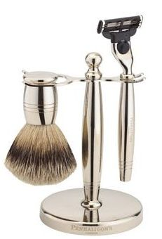 silver shaving brush and silver razor on a silver stand