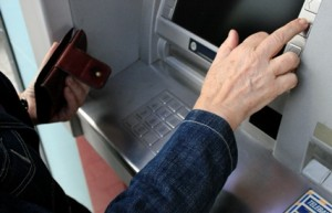 Woman in denim jacket withdrawing money from a cash machine