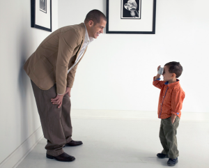 A young boy taking a photo of a man in a beige suit