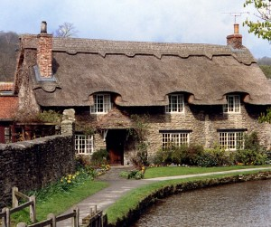 Large thatched cottage by a river