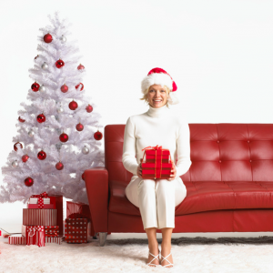 Woman sitting with present next to a white Christmas tree.