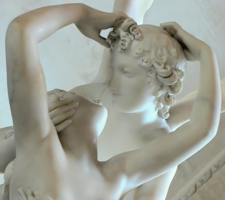 A statue of a man and woman kissing in while marble.