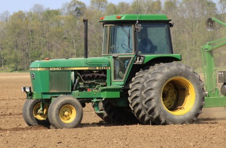 A John Deere tractor in a muddy field