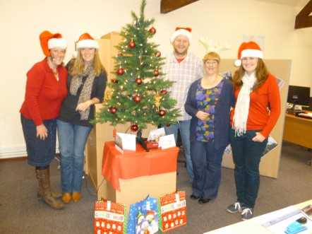 The Muddy Matches team posing in Christmas hats around a Christmas tree