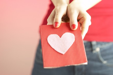 A woman holding a red Valentine's card with a pink heart on it