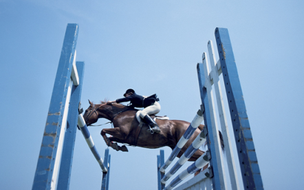 A horserider jumping over a jump.