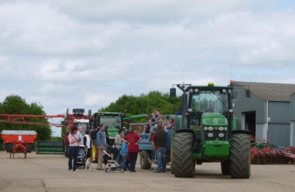 People queing for a trailor pulled by a green John Deer