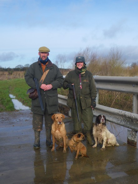 Man and woman in shooting gear with 3 dogs.