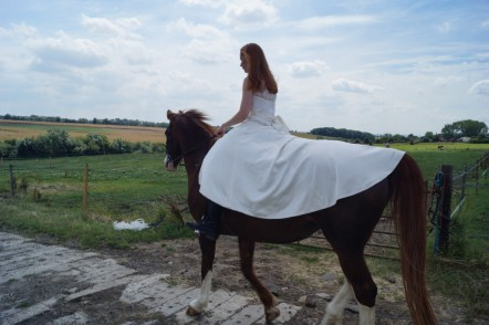 Back view of Sophie riding her horse in her wedding dress